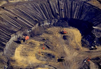Where once existed a Boreal forest, now an open pit oil sands mine worked by shovels and trucks.
